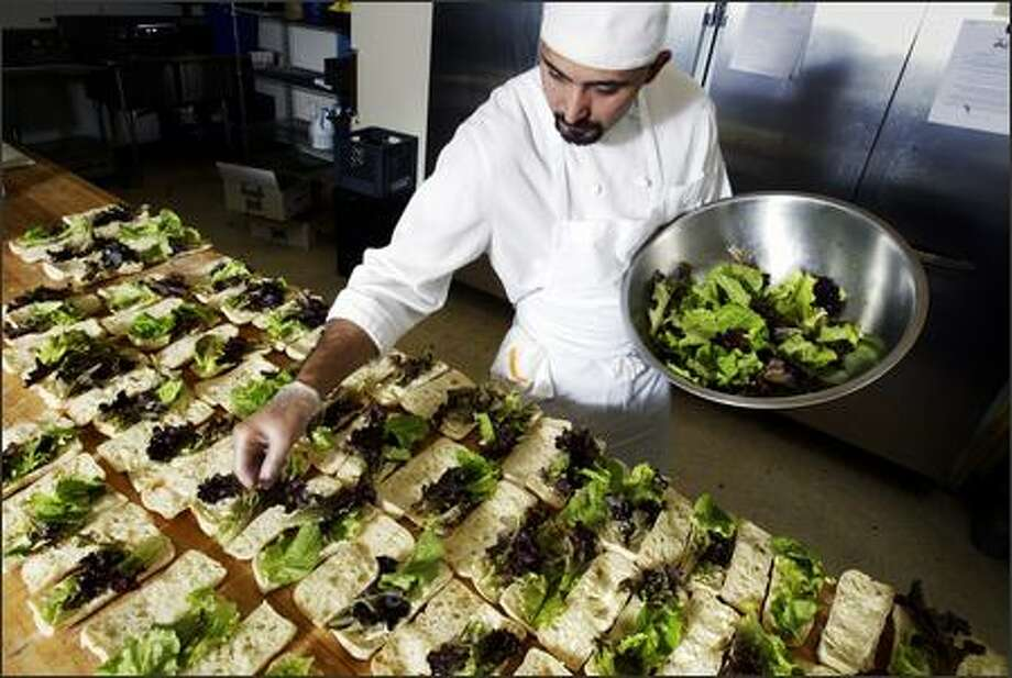 Herban Feast employee Juan Martinez adds baby lettuce from Willie Green's Organic Farm to some of the 220 sandwiches prepared at the catering business Tuesday. Photo: Andy Rogers/Seattle Post-Intelligencer