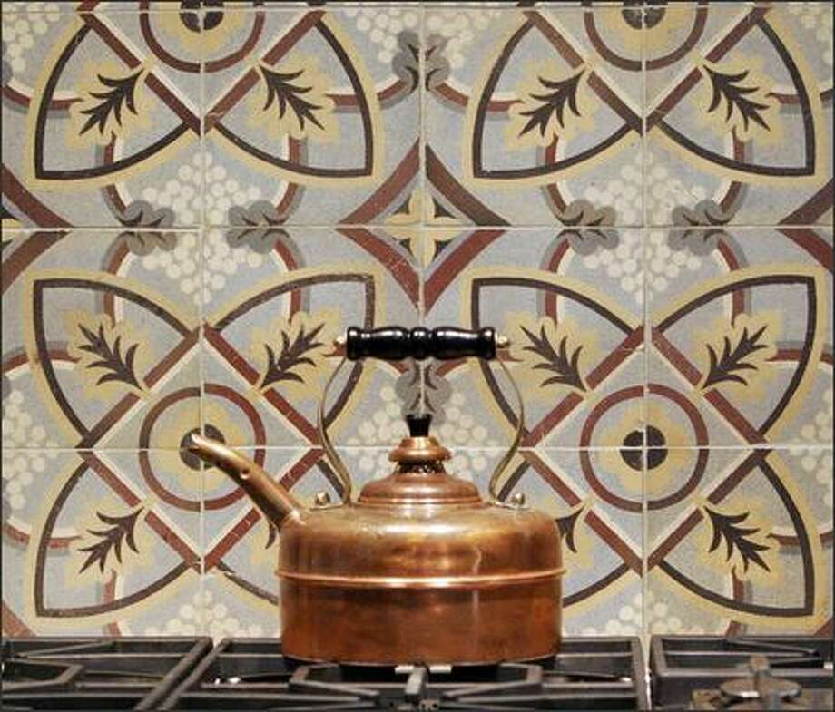 An antique kettle complements a stove with an antique tile wall in Maria Bartlett's kitchen. Photo: / Associated Press