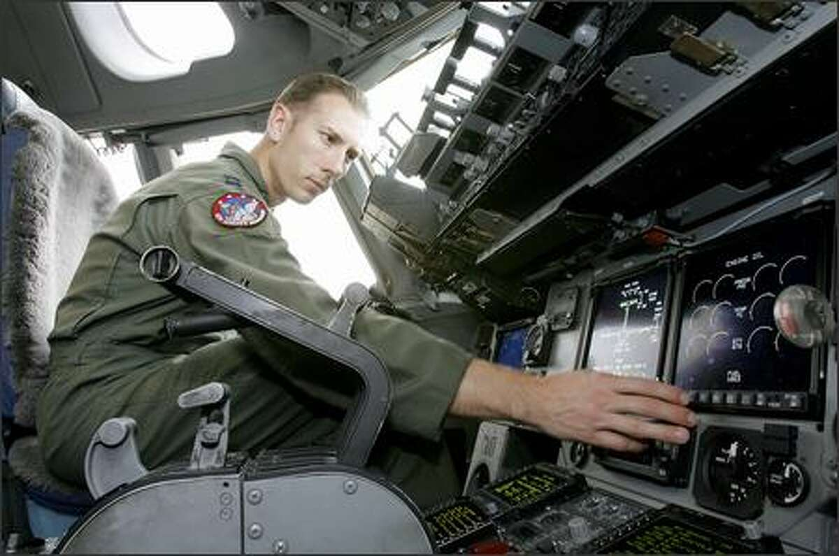 Capt. Nathan Higgins of the 4th Airlift Squadron sits in the cockpit of a C-17 airlifter during a tour at McChord Air Force Base.
