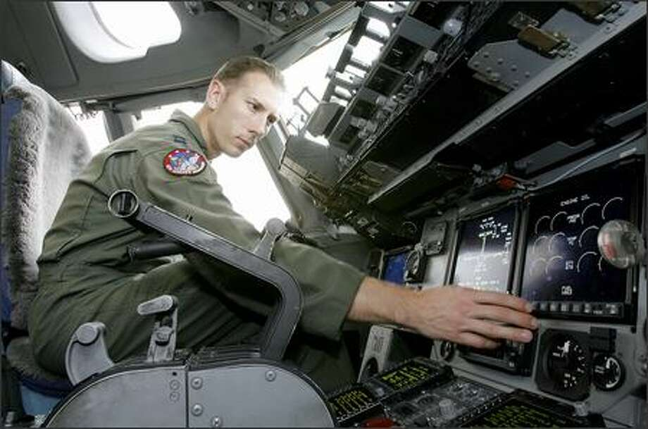 Capt. Nathan Higgins of the 4th Airlift Squadron sits in the cockpit of a C-17 airlifter during a tour at McChord Air Force Base. Photo: Gilbert W. Arias/Seattle Post-Intelligencer