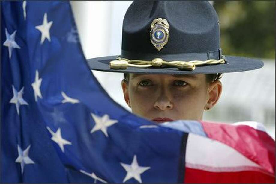 Everett police Officer Meg Nelson, a member of the flag detail, stands ready to raise the flag to half-staff during Friday's ceremony in Olympia. Photo: Gilbert W. Arias/Seattle Post-Intelligencer