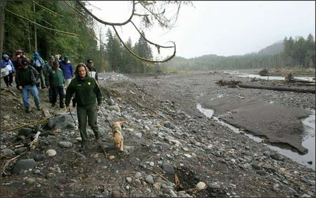 Lee Taylor (with Lira, a guide dog she's training), information officer at Mount Rainier National Park, shows volunteers where the Nisqually River breached levees during last November's storms and eroded about five acres of land at Sunshine Point, including 200 yards of roadway. The park reopens Saturday.