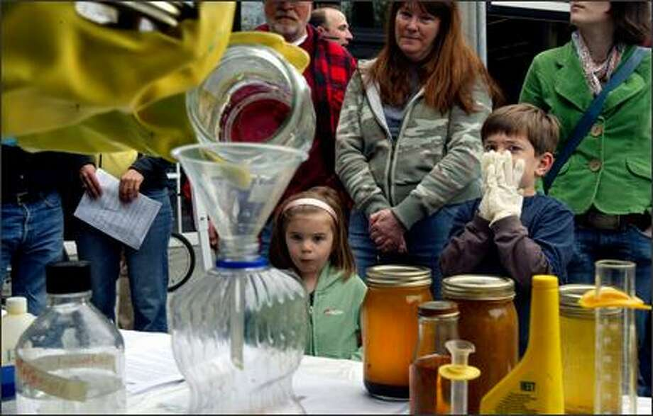 Tyler Hardie, 6, covers his face to avoid breathing the fumes as Ballard High School students combine methanol and potassium hydroxide with used cooking oil to create biodiesel fuel during a demonstration at the Northwest Biodiesel Forum. Hardie's sister Camille, 4, and Kandice Kelly look on as well. Tyler was wearing gloves in preparation for helping to mix the combined ingredients through vigorous shaking. His parents have been considering about switching to a biodiesel vehicle. Photo: Andy Rogers/Seattle Post-Intelligencer
