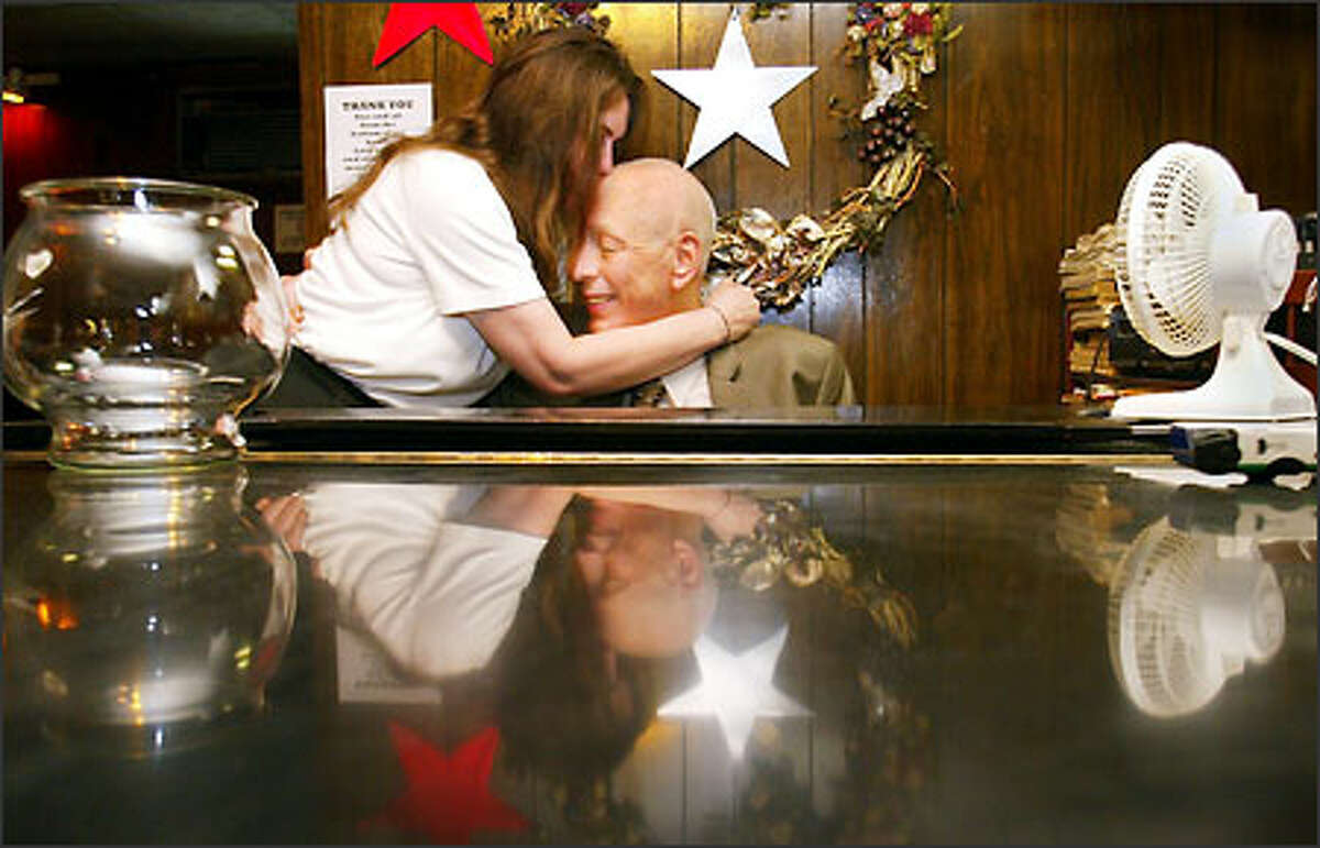 In this 2003 photo, Sorry Charlie's piano player Howard Bulson is kissed on the forehead by cocktail waitress Rose Stringer.