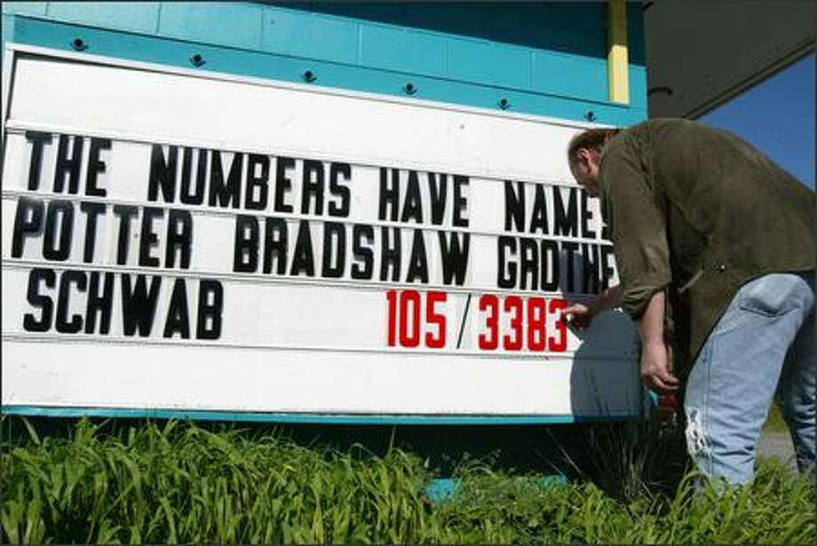 Restaurant manager Uwe Cook of Galloping Gerties in Lakewood, just outside Fort Lewis, changes the sign Monday bearing the number of soldiers killed in Iraq since the war began four years ago. On the left is the number of soldiers who have died from Fort Lewis, on the right the total death count. Photo: Karen Ducey/Seattle Post-Intelligencer
