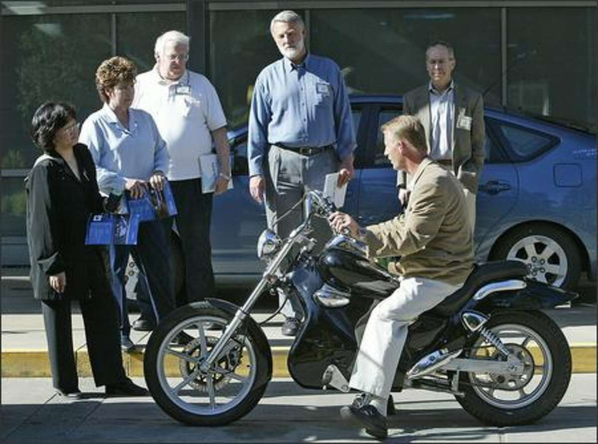 Frank Ziegler, hybrid technologies director of sales and distribution, demonstrates his company's all-electric motorcycle. He says it will travel up to 85 mph and travel 75 miles before needing a four-hour recharge. The bike was developed in Mooresville, N.C.