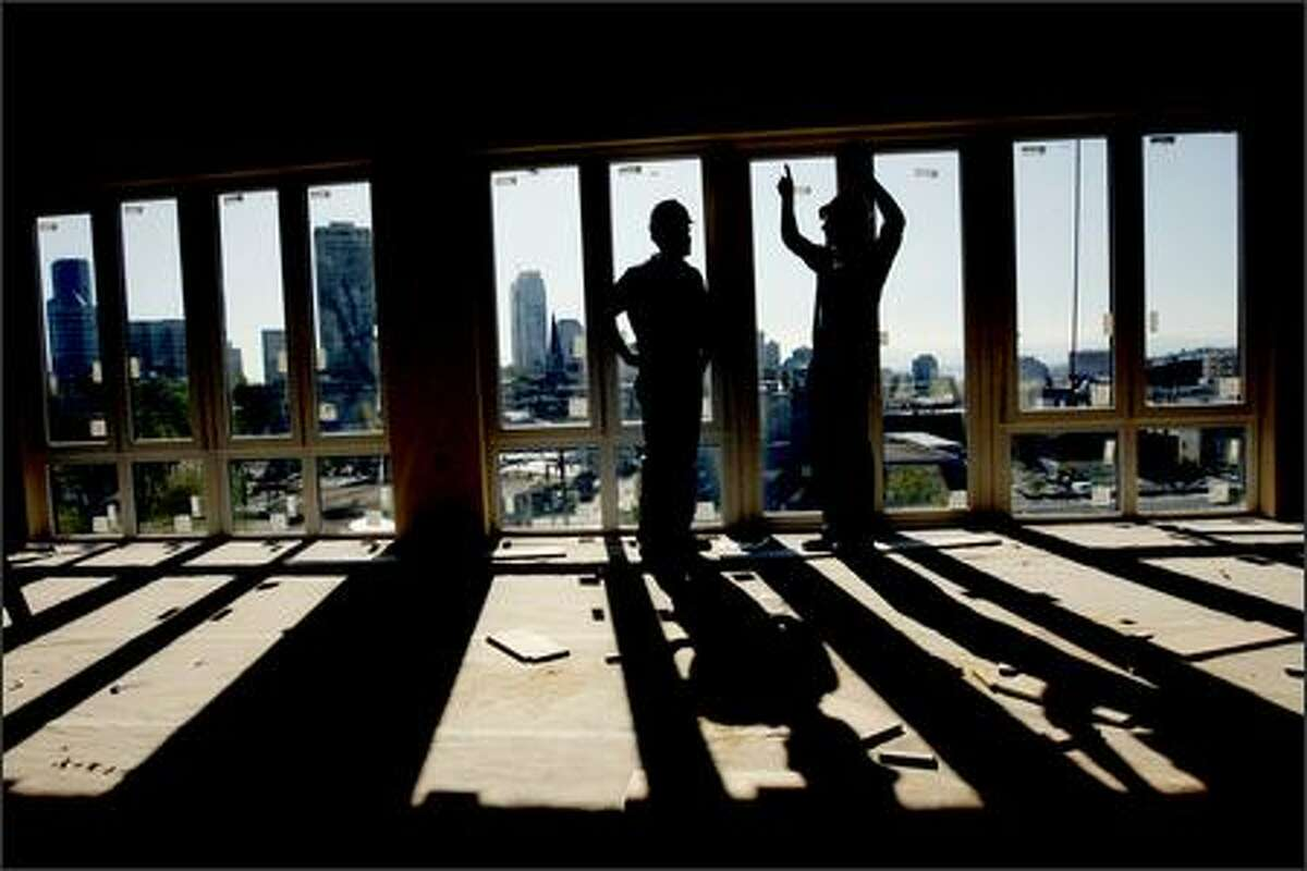 In a fifth-floor Trace Lofts condo with a view of downtown, developer Ted Schroth, left, and Edward Krigsman, of EK Real Estate, talk about the building's development. Schroth had to put layers of new materials on top of old wood floors to muffle sound -- and then, to preserve character, put new floors made out of old wood on top.