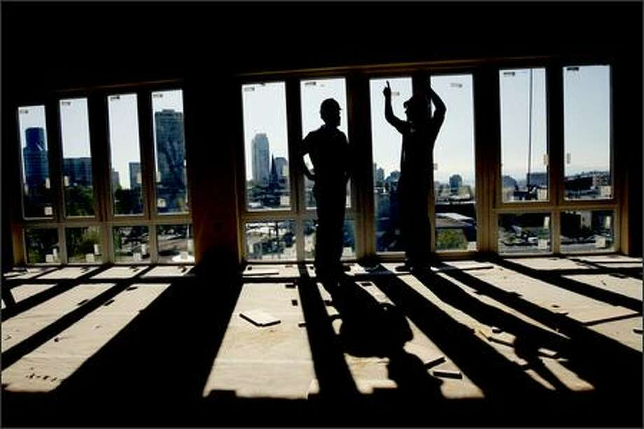 In a fifth-floor Trace Lofts condo with a view of downtown, developer Ted Schroth, left, and Edward Krigsman, of EK Real Estate, talk about the building's development. Schroth had to put layers of new materials on top of old wood floors to muffle sound -- and then, to preserve character, put new floors made out of old wood on top. Photo: Grant M. Haller/Seattle Post-Intelligencer