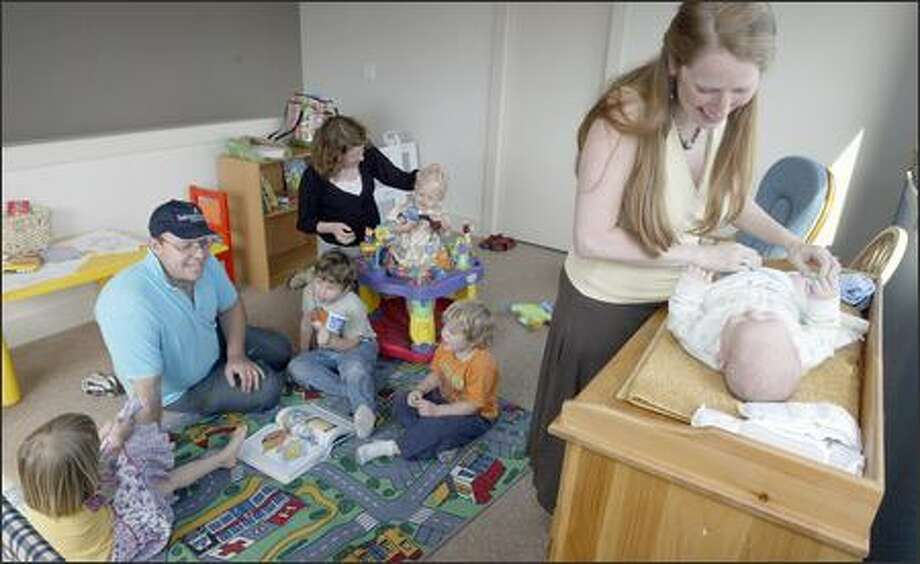 "Ruby Grynberg, right, owner of Salmon Bay Community Lending, diapers her 2-month-old son, Mateo Grynberg, while loan officer Colleen Butler, at back, plays with her 20-month-old son, Griffin Schwartz. While Grynberg works, husband Sebastian Grynberg minds the children. On the floor with him are two other sons, Zacarias, 5, left, and Alejandro, 3, and Griffin's 3-year-old sister, Rowan. ""It eliminates so many stresses,"" Ruby Grynberg says. Photo: Grant M. Haller/Seattle Post-Intelligencer"