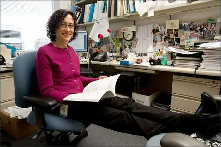 """Psychologist Evette Ludman leafs through a report in her Group Health office. She is the lead author of a major study published in April showing that over-the-phone therapy can help in alleviating depression. """"People opened up to phone therapists,"""" Ludman said. Photo: Grant M. Haller/Seattle Post-Intelligencer"""