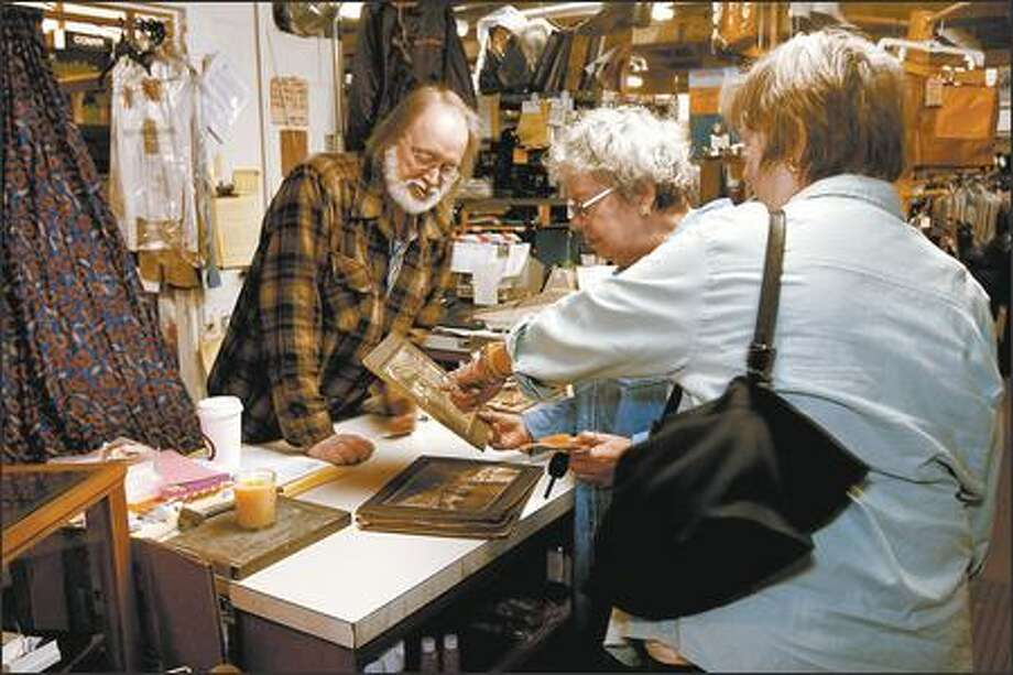 Larry Duncan, left, co-owner of Duncan & Sons, on Monday shows photos of the store from its glory days in the early 1900s to Sara-Jane Bellanca and Martha Gordon, right, longtime friends who stopped by to say goodbye. The store will close May 31. Photo: Grant M. Haller/Seattle Post-Intelligencer