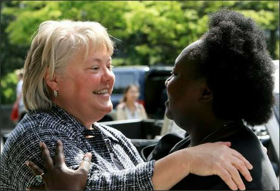 "Seattle University School of Law dean Kellye Testy, left, is greeted Tuesday by Anita Koyier-Mwamba, a former student in Testy's contract law class, on the school's campus on First Hill. Koyier-Mwamba said that after three years under Testy's tutelage at the law school, it would be impossible for graduates to lack a sense of social responsibility. ""It will always nag their conscience -- if they have one,"" she said. Photo: Dan DeLong/Seattle Post-Intelligencer"
