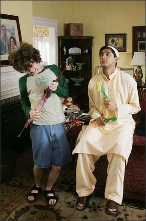 """Justin (Dan Byrd), left, and his family take in Raja (Adhir Kalyan), an exchange student from Pakistan, in The CW's """"Aliens In America."""" Rock the umbrella and scrubbers! Photo: The CW"""