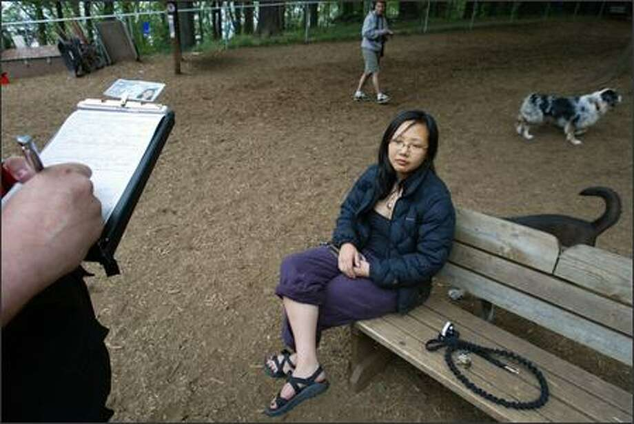 During a May 6 visit to the Golden Gardens off-leash area, Jennifer Tam gets a ticket for not having her dog Sylo licensed in the city of Seattle. Sylo was licensed in Oregon, and Tam said she didn't know there was a time limit on licensing the animal in a new place. She said she felt like she should have gotten a warning. Photo: Meryl Schenker/Seattle Post-Intelligencer