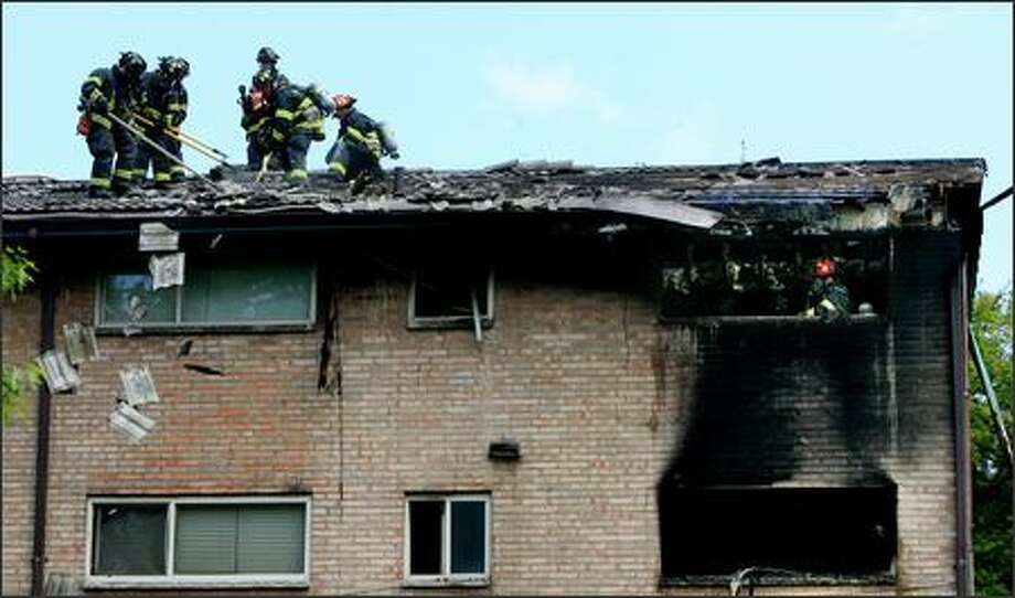Firefighters push tiles off the roof of the 20-unit apartment building at 3919 S. Pearl St. in South Seattle that was damaged Thursday by a fire started by a child playing with a lighter. No injuries were reported in the early afternoon blaze. Photo: Dan DeLong/Seattle Post-Intelligencer