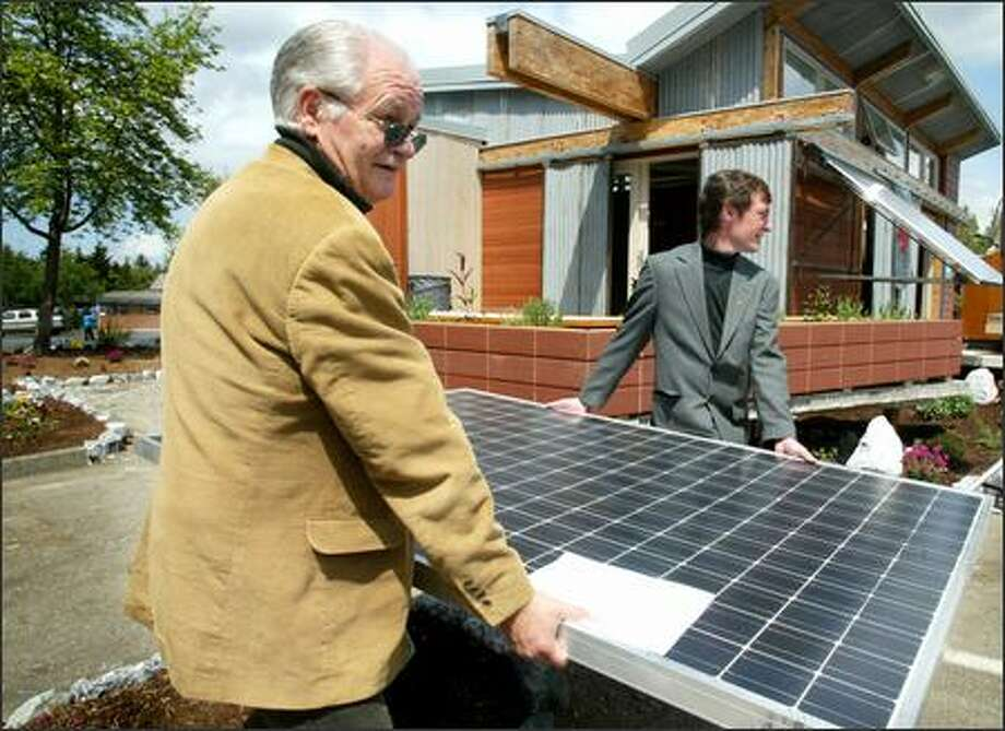 Mike Nelson, director of the Northwest Solar Center, and Mat Taylor, professor of architecture and construction management at Washington State University, carry a solar panel Thursday to the Zero Energy House at Shoreline Community College. Photo: Paul Joseph Brown/Seattle Post-Intelligencer