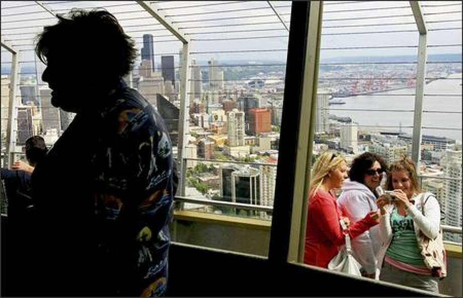 Carmen Viig, lead tour guide at the Space Needle, talks with visitors Friday on the observation deck of the Seattle Center landmark. The 45-millionth visitor is expected to ride the elevator to the top this weekend ... and win a pair of tickets to Paris. Photo: Dan DeLong/Seattle Post-Intelligencer