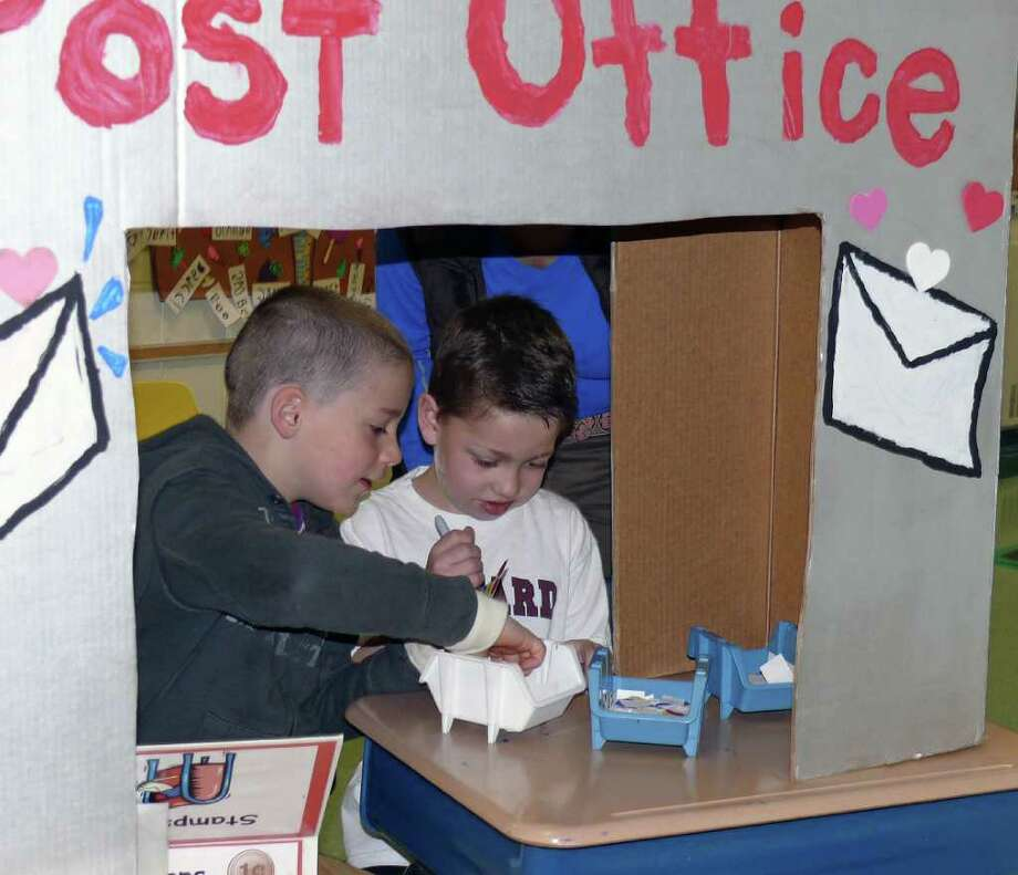 """Finn Hoey, left, and fellow first grader Sam Frank go over their supply of """"stamps"""" at the Osborn Hill School post office Monday. Photo: Genevieve Reilly / Fairfield Citizen"""