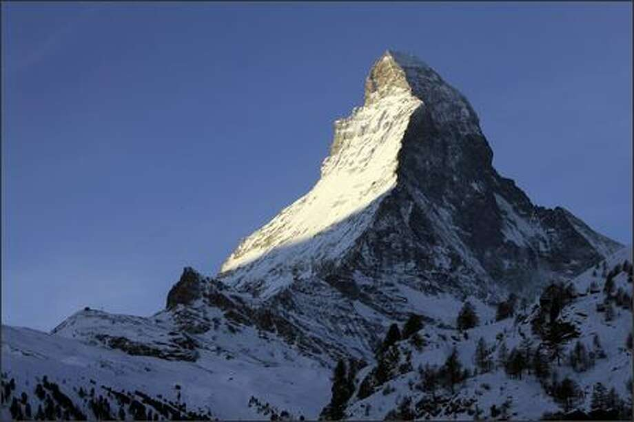 The rising sun illuminates the Matterhorn. At 14,690 feet, it's not the highest Swiss mountain, but it surely is the most photogenic. Photo: / Associated Press