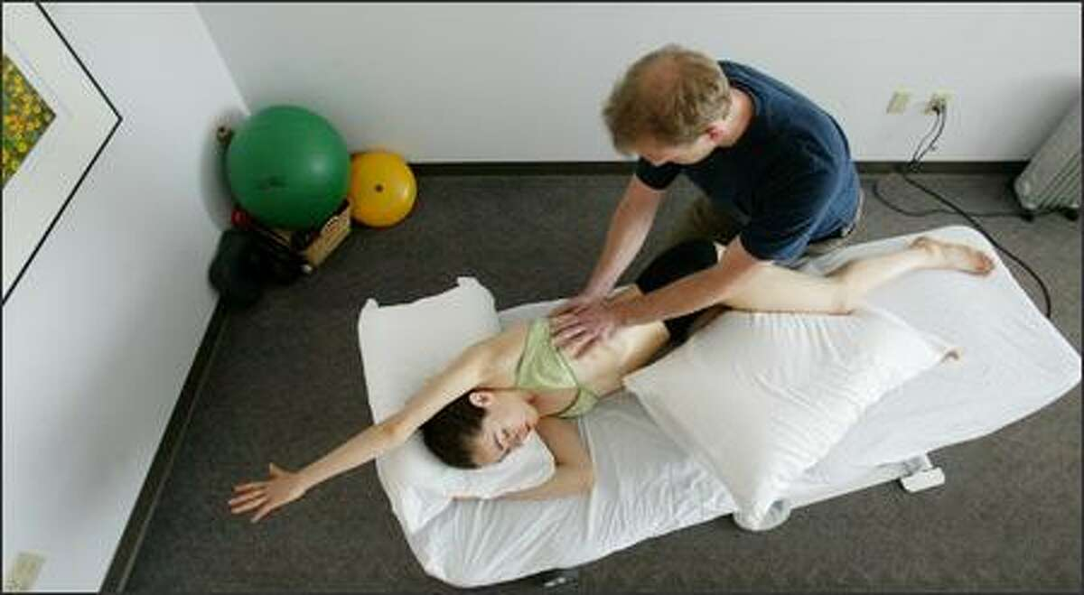 Brad Jones, a certified advanced Rolfer, works on Zoe Scofield, a dancer, at his office in Fremont.