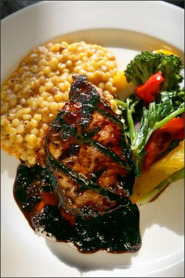 The pork loin chop has a cherry balsamic glaze and comes with roasted yellow pepper couscous. Most of the food served here is organic, local and seasonal. Photo: Scott Eklund/Seattle Post-Intelligencer