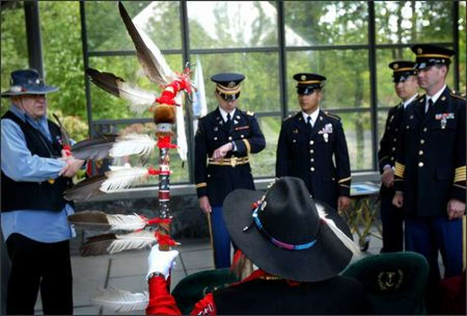 Robert Sison, holding a staff with 80-year-old eagle feathers, waits with Army National Guard members from Camp Murray and fellow Inter-Tribal Honor Guard member Warren Gohl for a military funeral at Tahoma National Cemetery. Photo: Joshua Trujillo/Seattle Post-Intelligencer