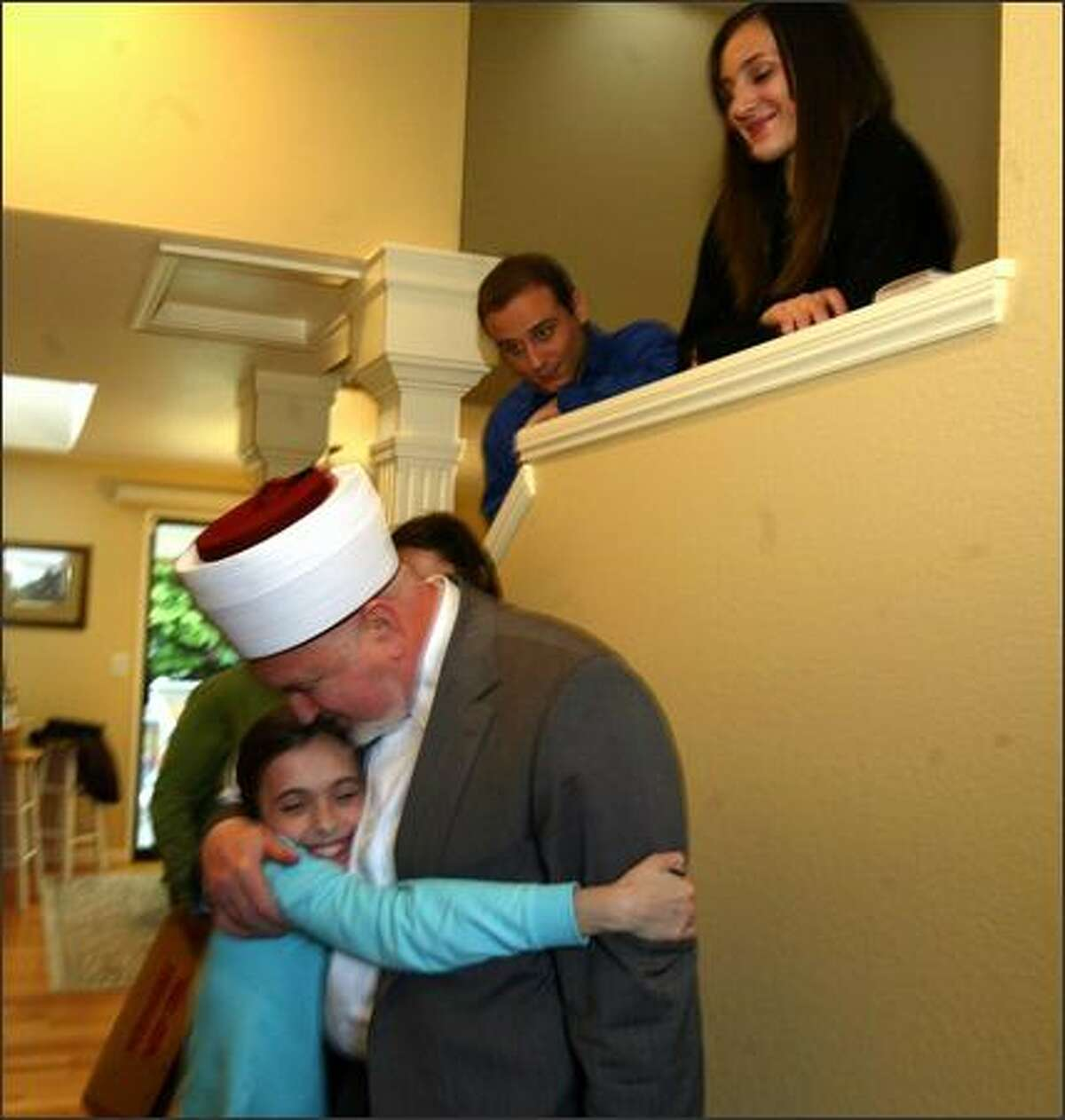 Farrah Saracevic, 10, hugs Grand Mufti Mustafa Ceric after he visited her Lynnwood home Sunday. Farrah's dad, Muhamed Saracevic, is local president of the Congress of North American Bosniaks. Muhamed's other daughter Hanan Saracevic is right. Left of her is family friend Nedzad Taljanovic.