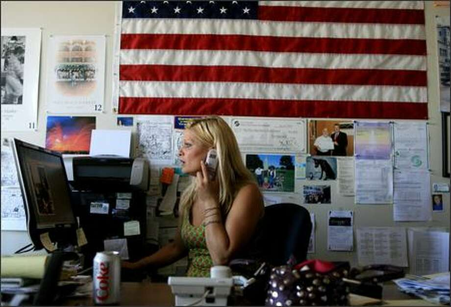"Megan Lee of the Pike Place Market News makes a call in her office. The News aims to capture what Lee calls the ""city within the city."" Photo: Meryl Schenker/Seattle Post-Intelligencer"