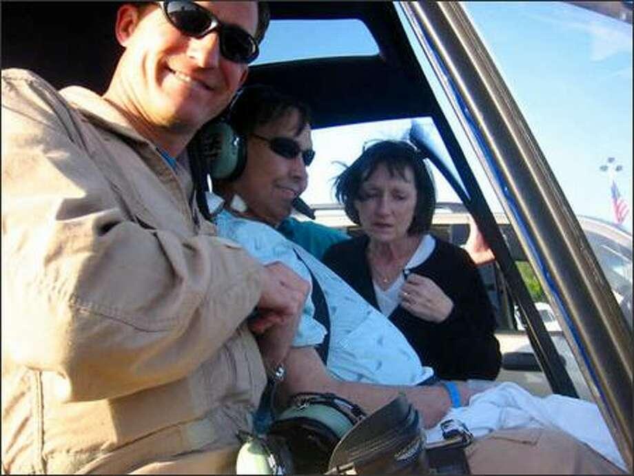 Rob Lutz, center, with his wife, Ida Lutz, and pilot Ed Hrivnak, prepare for Lutz's final flight. Hrivnak flew his longtime friend over the Green River toward Mount Rainier.