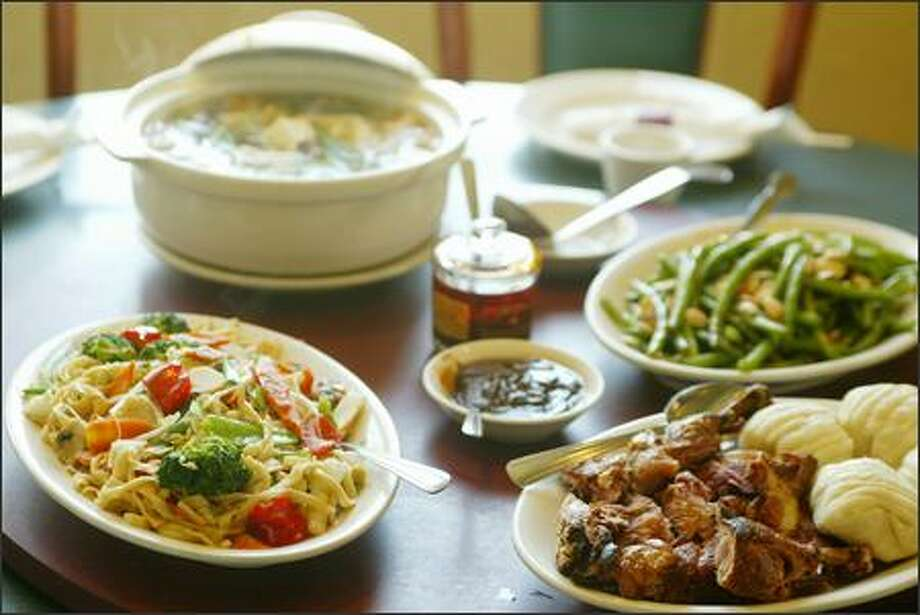 A sampling of Judy Fu's generous dishes includes, clockwise from lower left, chow mein whith homemade egg noodles and vegetables, Land and Sea Stew, dry-sauteed string beans with almonds, and Dave's Crispy Smoked Duck. Photo: Paul Joseph Brown/Seattle Post-Intelligencer