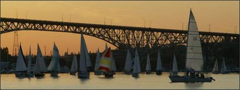 Sailboats race in the organized chaos of a recent Duck Dodge on Lake Union as dusk settles in behind the Aurora Bridge. Photo: Joshua Trujillo/Seattle Post-Intelligencer