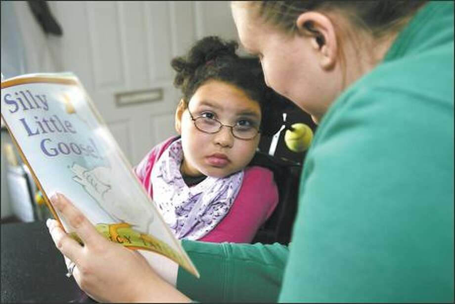 "Devin Cabbage, 9, listens from her wheelchair as caretaker Christine Benson reads ""Silly Little Goose"" after school Wednesday. Devin, who has cerebral palsy, lost her main mode of transportation when a man, eluding police, crashed into the rear of her empty wheelchair-accessible van. Photo: Grant M. Haller/Seattle Post-Intelligencer"