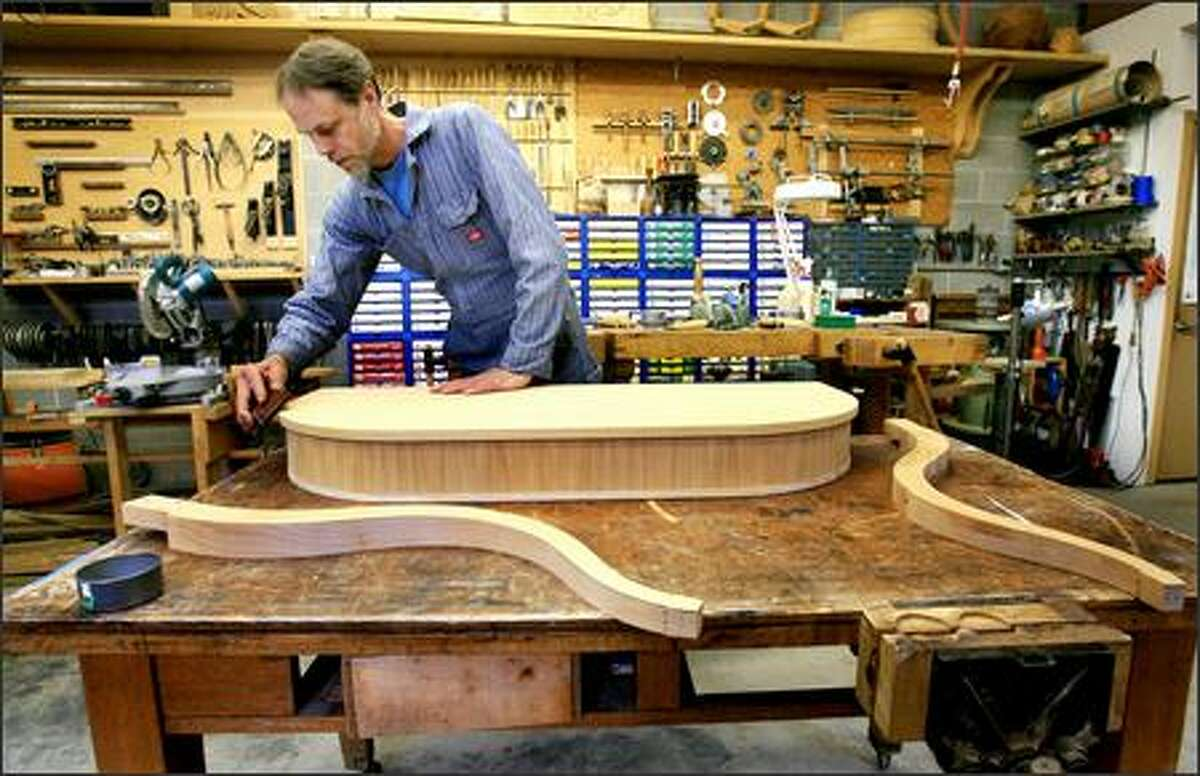 Furniture maker Stephen Hultberg sands a handcrafted custom console he's making for a client.