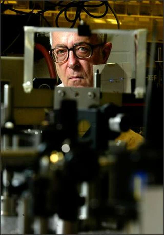John Cramer, a physicist at the University of Washington, is reflected among some of the materials he's using for an experiment that challenges the traditional concept of time. The public has donated $35,000 to his research. Photo: Andy Rogers/Seattle Post-Intelligencer