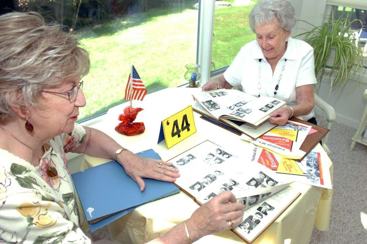 """Betty Collins, left, and Shirley Madden look through their 1944 Stratford High School yearbooks in Madden's Shelton home. They have helped organize a """"fabulous forties"""" renunion for graduates of the school."""