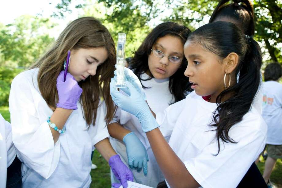 Cloonan Middle School seventh graders Amanda DiCicco, 11, left, Debbie Pinto, 12, center, and Janel Rivera, 12, right measure the salination level of the Mill River from a sample they took as part of a World Water Monitoring Day. Photo: Kerry Sherck / Stamford Advocate