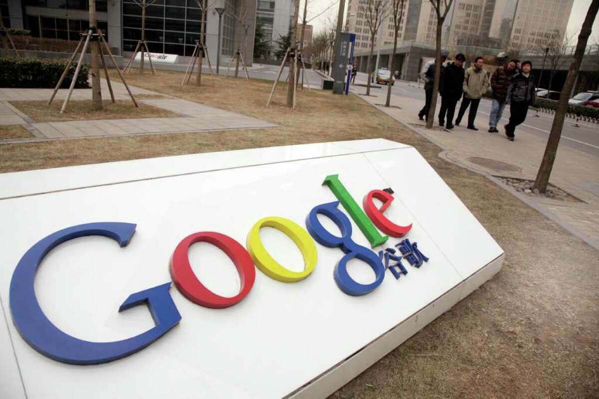FILE -- In a Monday March 22, 2010, file photo men walk past the Google China headquarters in Beijing, China. Google said Monday, March 21, 2011, the Chinese government is interfering with its email services in China, making it difficult for users to gain access to its Gmail program, amid an intensified Internet crackdown following widespread unrest in the Middle East. (AP Photo/Ng Han Guan/file)