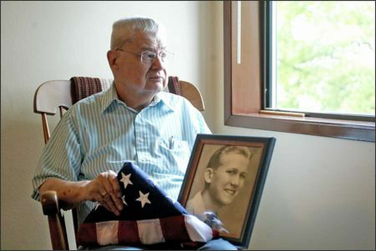 """Chuck Lazenby and his partner, David Asplund (in the framed picture), kept their relationship secret for 50 years. Lazenby received the American flag after a screening of """"Inlaws & Outlaws,"""" which features their relationship. Although Asplund served in World War II, the military would not give the flag to Lazenby after Asplund's death because a domestic partner could not receive the same benefits as a family member."""