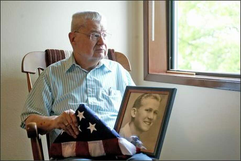 "Chuck Lazenby and his partner, David Asplund (in the framed picture), kept their relationship secret for 50 years. Lazenby received the American flag after a screening of ""Inlaws & Outlaws,"" which features their relationship. Although Asplund served in World War II, the military would not give the flag to Lazenby after Asplund's death because a domestic partner could not receive the same benefits as a family member. Photo: KAREN DUCEY/P-I"