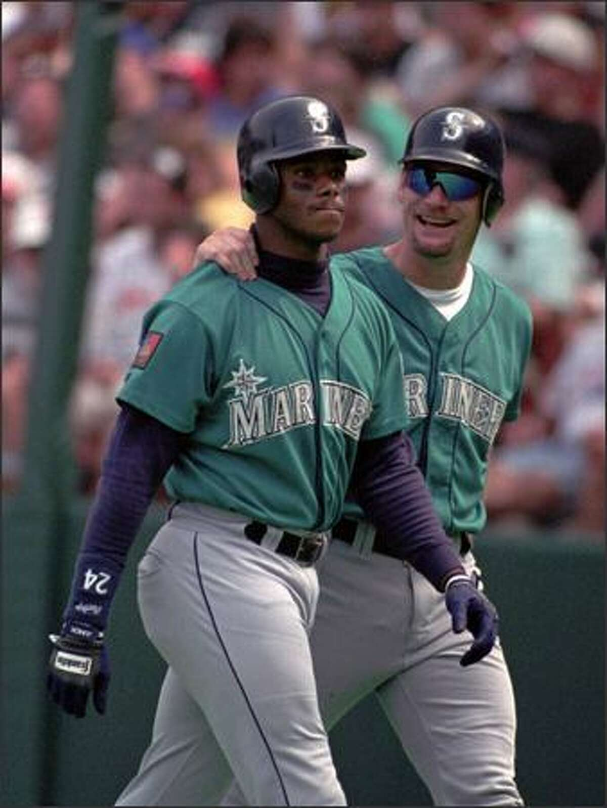 Ken Griffey Jr. gets a pat from Jay Buhner as they leave the field after a home run by Griffey in 1994.