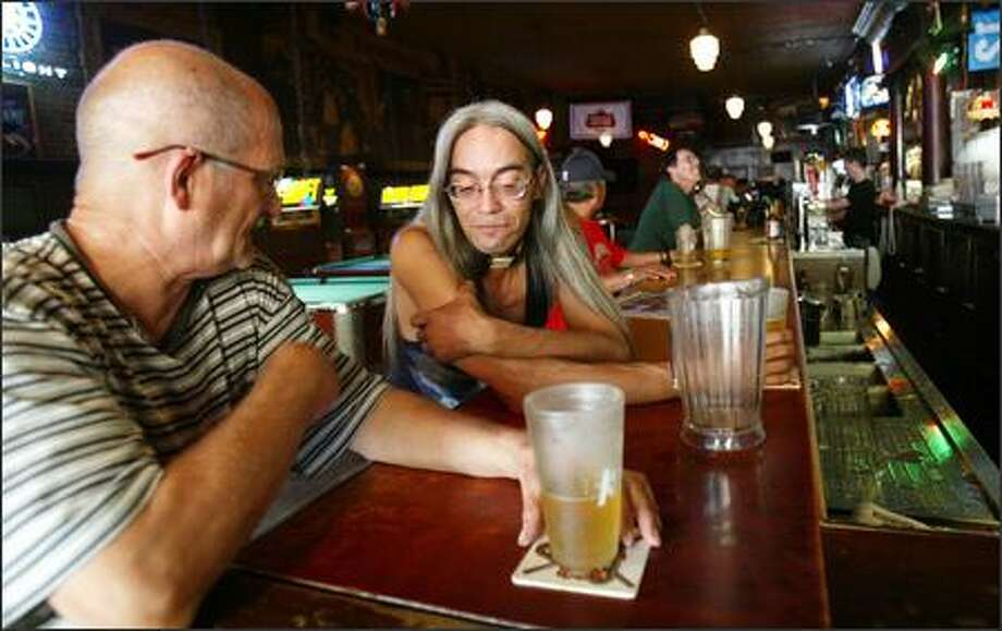 Wally Glaspey, left, and Thomas Anderson chat Wednesday at the Double Header tavern in Pioneer Square. The tavern was once a hangout for transvestites, but it is no longer considered a gay bar. Photo: Karen Ducey/Seattle Post-Intelligencer