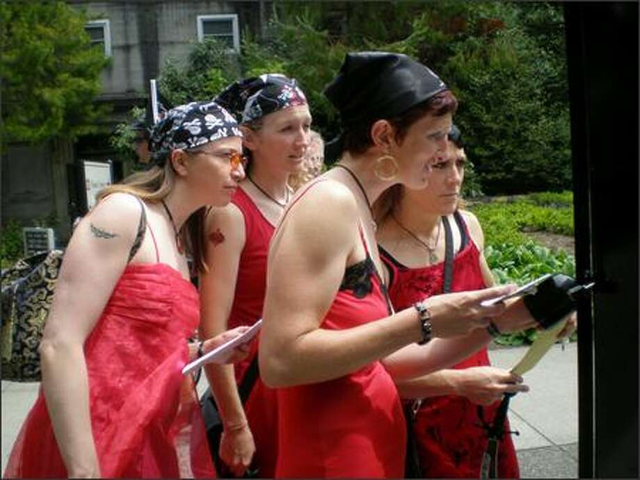 From left, Suzanne Dolberg, Liz Woodcock, Laura Silverton and Lauren Reynolds -- aka the Ravishing Red Raiders -- check out the Ballard Locks information map to find answers to scavenger hunt clues. The scavenger hunt was held by Seattle Inner City Outings to raise money for and awareness of their organization. Photo: Kate Elston/P-I