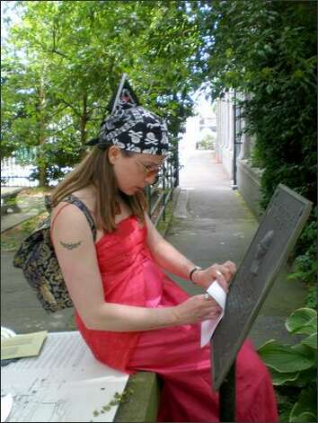 Suzanne Dolberg takes a rubbing of a plaque at the Ballard Locks -- one of the many tasks her team and 20 others had to perform to rack up points in Seattle Inner City Outings' scavenger hunt fundraiser. Photo: Kate Elston/P-I
