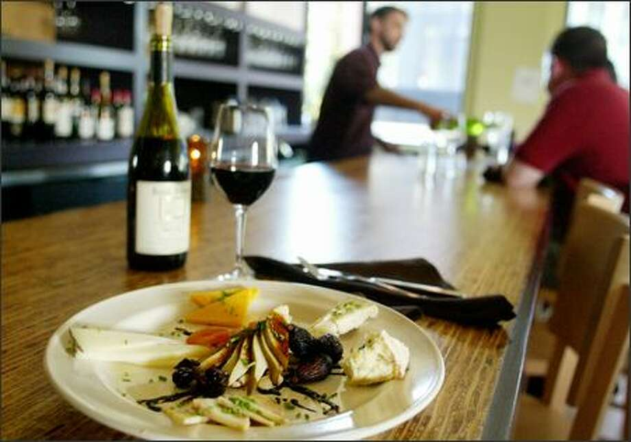 A mixed cheese plate is accompanied by a Cotes de Rhone. Although its menu can be uneven, Verve also offers a fantastic crostini plate, with duck prosciutto, goat cheese and smoked salmon. Photo: Paul Joseph Brown/Seattle Post-Intelligencer