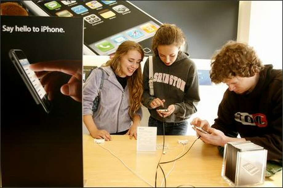Maddie Hall, left, Kelly Pettit and John Worthington try out demonstration iPhones at the University Village Apple Store while Maddie's father was in line to buy the phone. More than 300 people waited to buy the touted iPhone at the store, which opened at 6 p.m. Friday. Photo: Grant M. Haller/Seattle Post-Intelligencer