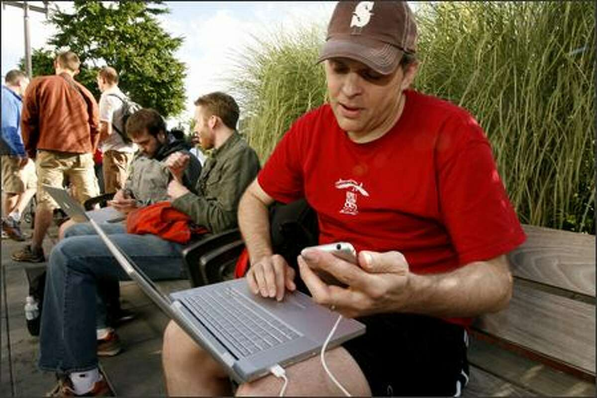 Chris Fassel downloads the latest system software that he needs before he can activate his new iPhone. More than 300 people were in line Friday to buy the new Apple iPhone at the University Village Apple store. The gadgets combine a phone, a music player and the Internet.