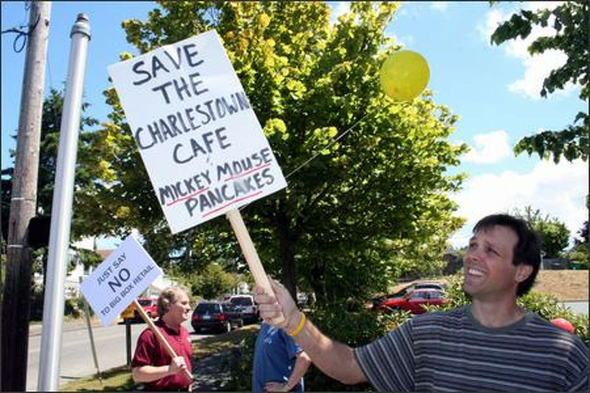 Webster's Charlestown Street Café co-owner Larry Mellum, left, holds a protest sign with West Seattle resident Matt Whittemore. About a dozen West Seattle residents rallied Saturday on California Avenue Southwest to prevent a Petco from being built on the site.