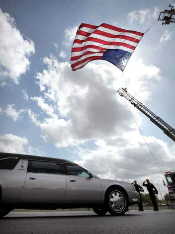 Metro daily  - Members of the San Antonio Fire Department salute as the hearse carrying fallen San Antonio Police Officer Stephanie Ann Brown, drives under a large American Flag supported from two fire trucks on 281 as it approaches 1604.  Monday, March 21, 2011. Photo Bob Owen/rowen@express-news.net Photo: Bob Owen, San Antonio Express-News / rowen@express-news.net
