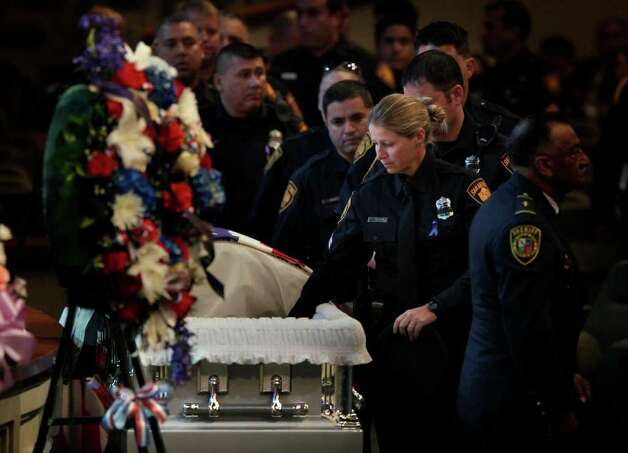 Metro daily  - A San Antonio police officer reaches to touch fellow fallen officer Stephanie Ann Brown during her funeral service at Community Bible Church, Monday, March 21, 2011. Photo Bob Owen/rowen@express-news.net Photo: Bob Owen, San Antonio Express-News / rowen@express-news.net