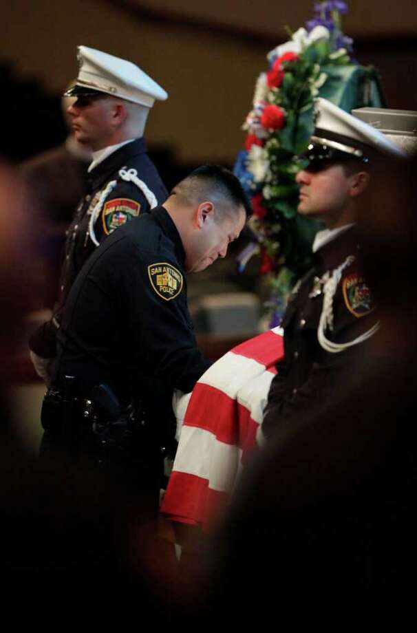 Metro daily  - SAPD's Roger De La Rosa, father of Stephanie Ann Brown's daughter, pays his respects to fellow officer Brown at the funeral service for San Antonio Police Officer Stephanie Ann Brown, at Community Bible Church, Monday, March 21, 2011. Photo Bob Owen/rowen@express-news.net Photo: Bob Owen, San Antonio Express-News / rowen@express-news.net
